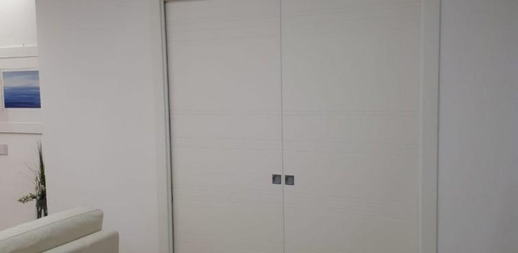 Porta scorrevole a due ante, laccata incisa, finitura bianco con telaio minimal